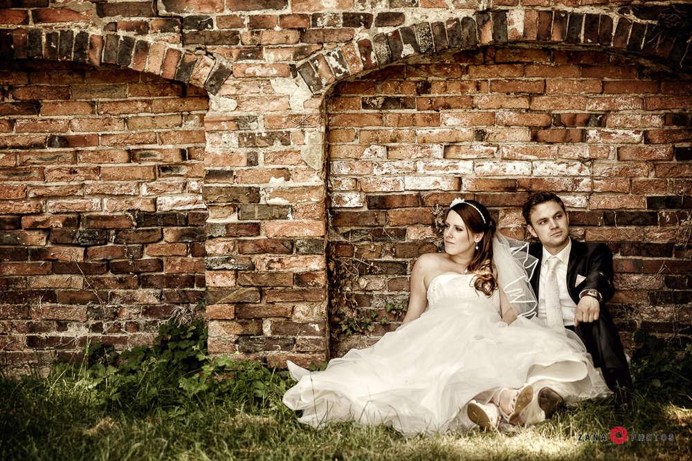 Hochzeitsfotograf-Braunschweig / Hochzeitspaar-an-der-Mauer-sitzend (ZANAPHOTOS)