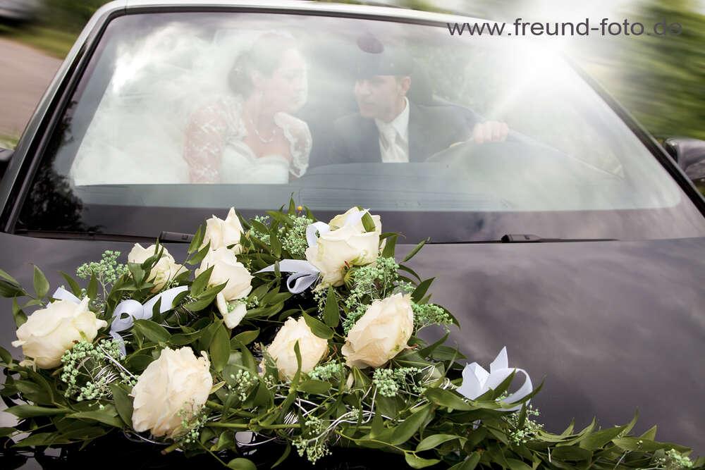 Brautpaar im Hochzeitsauto / Auf in die Flitterwochen (Freund Foto)